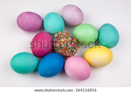 colored easter eggs and one covered with sprinkles isolated on white - stock photo