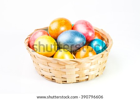 Colored Easter eggs in a basket on a white background.
