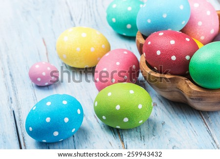 colored Easter eggs on wooden background. Focus on a green egg - stock photo