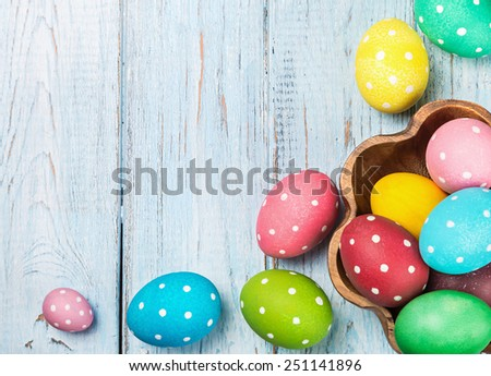 colored Easter eggs on wooden background. Focus on blue wooden background. - stock photo