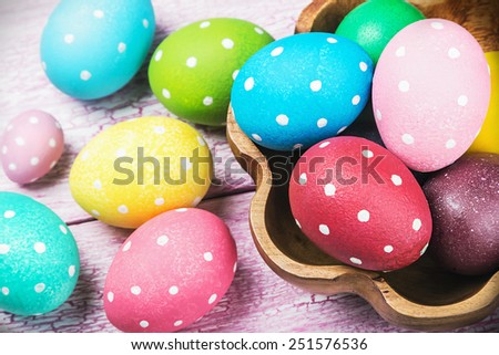 colored Easter eggs on wooden background. Focus on purple background. - stock photo