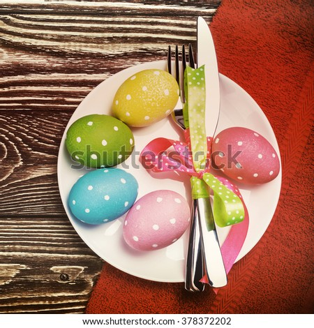 colored Easter eggs on wooden background. focus on the plate with eggs. toned image - stock photo