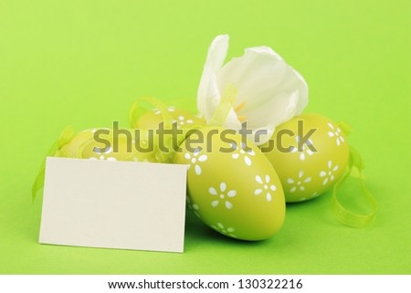 Colored eggs and beautiful white  tulips with card for your text on green background on Easter - stock photo