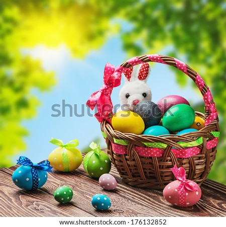 colored eggs in the basket on the table against the background of the garden - stock photo