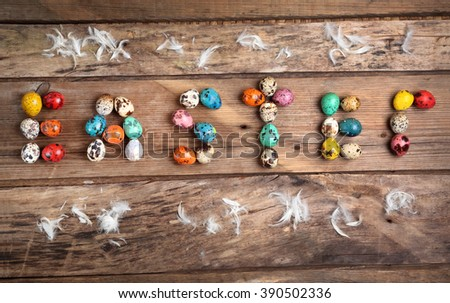 colored eggs in the form of the word Easter on an old wooden table - stock photo