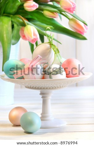 Colored eggs with bows and tulips for Easter - stock photo