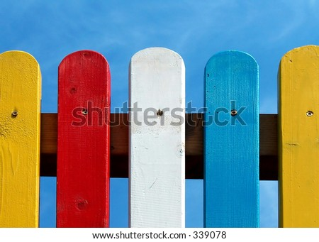 colored fence on clear blue sky background - stock photo