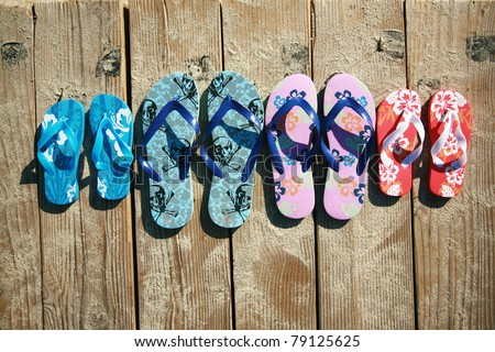 Colored flip-flops of a family of four by the beach at the ocean - stock photo