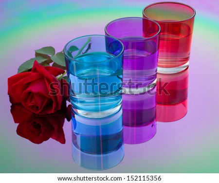 colored glasses of water are reflected in the color table mirror