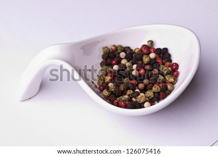 colored grains of pepper in a bowl. closeup on pastel background