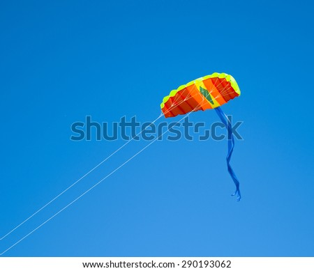 Colored kite flying in the blue sky - stock photo