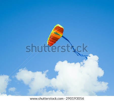 Colored kite flying in the blue sky with clouds - stock photo