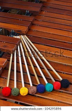 Colored marimba mallets resting on a marimba - stock photo