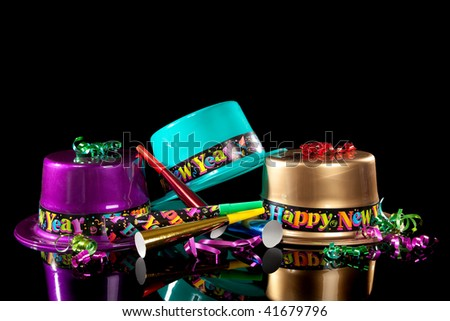 Colored New Years Eve hats including green, purple, pink gold and red, streamers, noise makers and confetti on a black background - stock photo