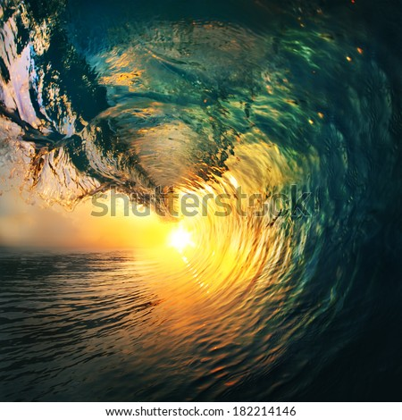 Colored ocean wave breaking at sunset. - stock photo