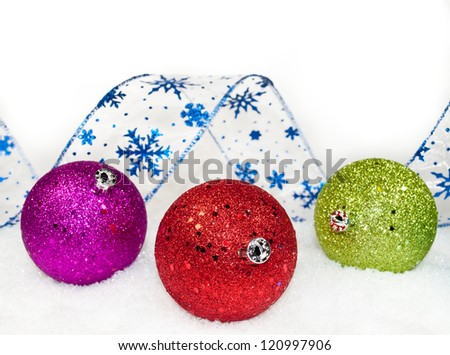 colored ornaments and ribbon in the snow - stock photo