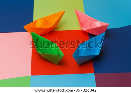 Colored paper boats on the colorful background. - stock photo