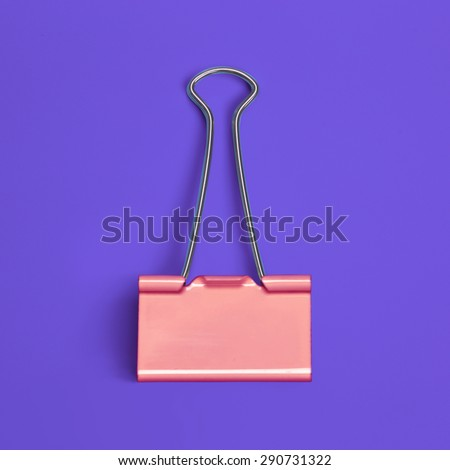 Colored paper clip view from above on colored background - stock photo