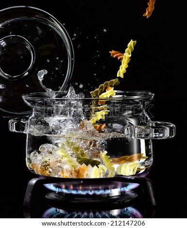 colored pasta falling in a glass saucepan on a gas stove - stock photo