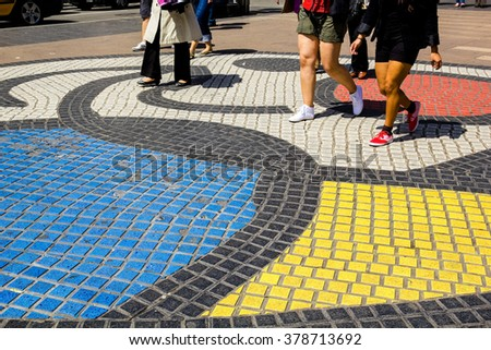 Colored pavement and people walking on the Ramblas of Barcelona - stock photo