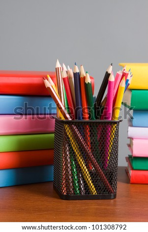 Colored pencils and a stack of books on the table