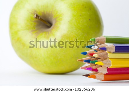 colored pencils and apple on white background - stock photo