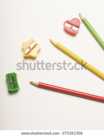 Colored pencils and sharpeners/Pencils and Sharpeners/Pencils and sharpeners on white surface - stock photo