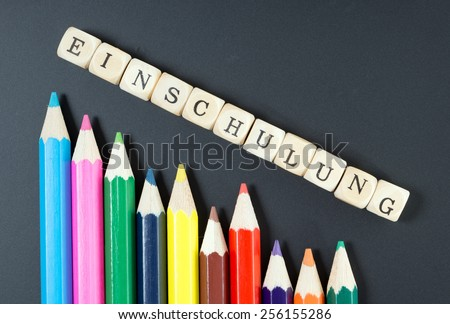 Colored pencils and wood dice with the german word school enrollment / school enrollment - stock photo