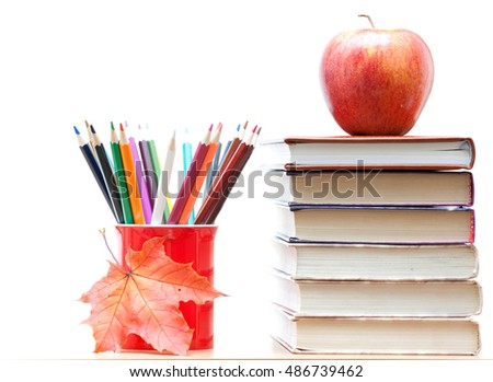 Colored pencils in a mug, the book and an apple