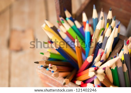 Colored pencils in wooden crates - stock photo