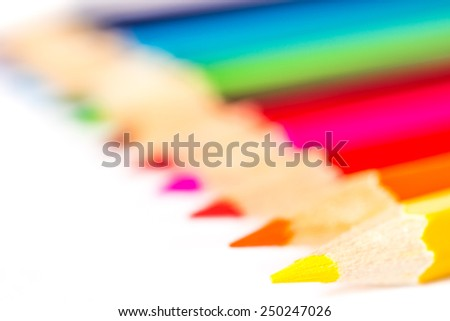 Colored pencils on an isolated background. Focus on the yellow pencil, close up view