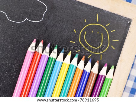 Colored Pencils on Chalk Board with Happy Sun Drawing - stock photo
