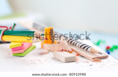 colored pencils, ruler, pencil sharpener on a white sheet of paper with wood shavings - stock photo