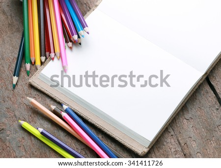 Colored pencils with blank sketch book on wooden background,education concept. - stock photo