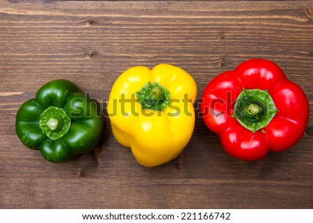 Colored peppers on wood top - stock photo