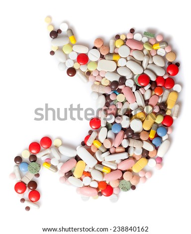 Colored pills, tablets and capsules on a white background in the form of a stomach - stock photo