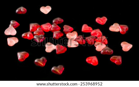 Colored (pink, red and orange), transparent heart shape jellies, black background, isolated. - stock photo