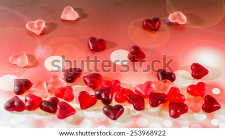 Colored (pink, red and orange), transparent heart shape jellies, red bokeh lights background. - stock photo