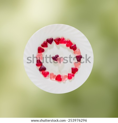 Colored (pink, red and orange), transparent heart shape jellies with ceramic plate, green degradee background, isolated. - stock photo