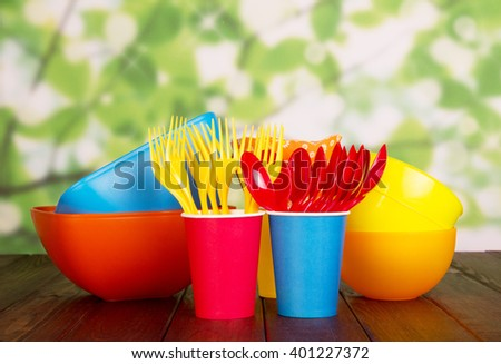 Colored plastic tableware: bowls, forks, spoons and paper cups on abstract green background. - stock photo