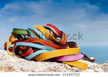 Colored ropes on the rock against the blue sky  - stock photo