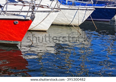 Colored sail boats parked on the dock of a lake. Red, white, blue, colors, reflections on water. - stock photo