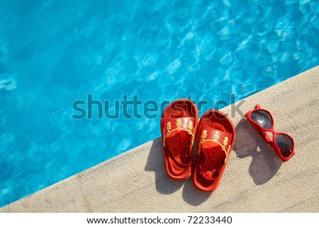 Colored sandal and sunglasses by the swimming pool - stock photo