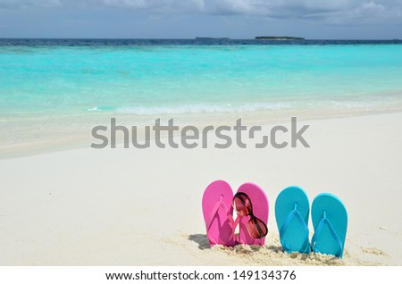 Colored sandals and sunglasses on sandy beach -- Vacation Concept  - stock photo