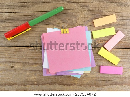 Colored stickers and pen on old wooden table - stock photo