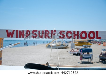 colored text that indicates the presence of a windsurfing school - stock photo