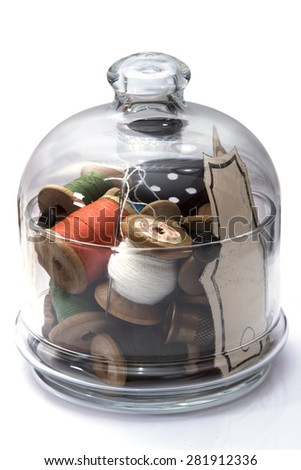 colored thread for sewing on wooden spools, needles, buttons, metal thimble stacked in transparent glass jar, sewing, hobby, on white background - stock photo