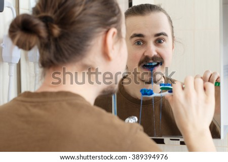 Colored tooth brush April Fools joke on young man - stock photo