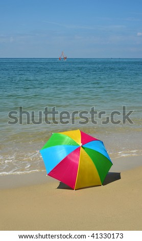 Colored umbrella isolated on beach - stock photo