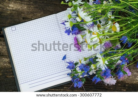 Colored wildflowers and a notebook to record with free space for text. Good for holiday greetings - stock photo